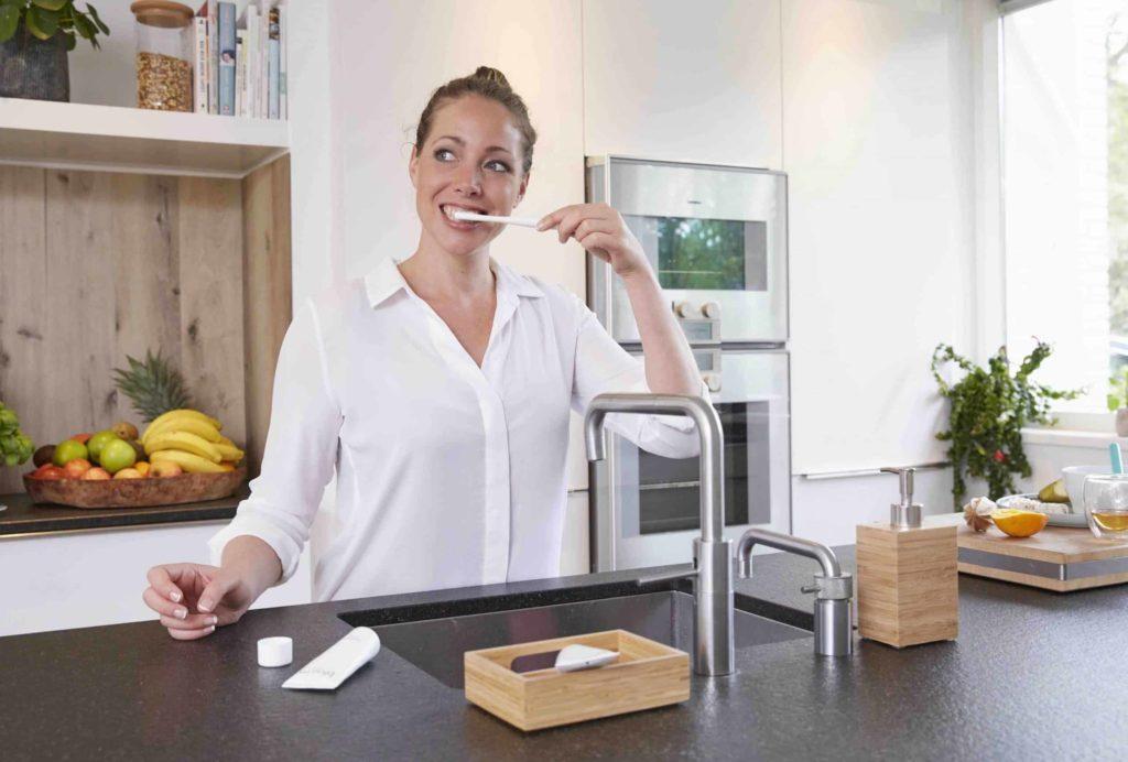 woman brushing teeth in kitchen